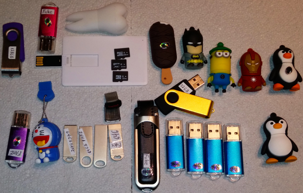 Two dozen fake USB and SD storage devices, all purchased on eBay, from sellers in Asia.